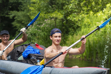 Young athletic men in boat rowing oars along the river on summer day. Canoe. Friends are swimming in a kayak. Active recreation in nature. Healthy lifestyle