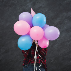 Girl in party hat hiding behind balloons
