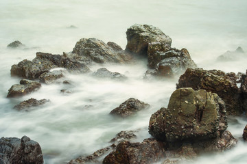 Long exposure seascape with foamy waves splashing against a rocky shore of thailand in the morning time.
