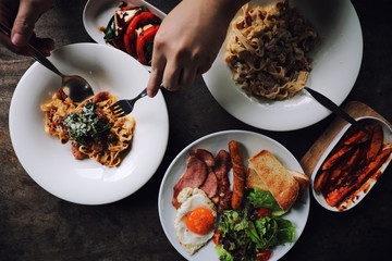 food flat lay top view with pasta and english breakfast on wood background