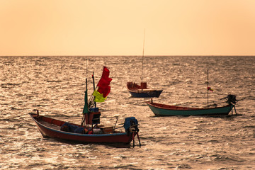 Floating fishing boats aground at the harbor in the sea sunset time at Chanthaburi, Thailand.