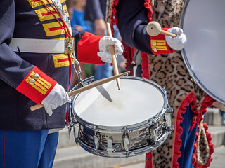Hands with sticks of old style soldier beating a drum