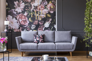 Grey lounge with patterned cushion in real photo of dark living room interior with floral wallpaper, molding on wall and gold lamp