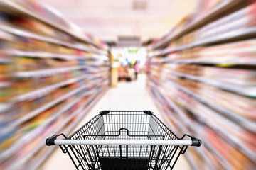 Shopping trolley in department store with consumer goods product on shelf background, Abstract motion blurred concept