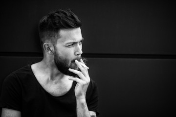 A young handsome white bearded man in black t-shirt smokes a cigarette in the street in the spring. Close up. Black and white.