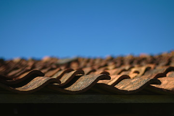 Macro view to roof tiles with a deep blue sky in the background
