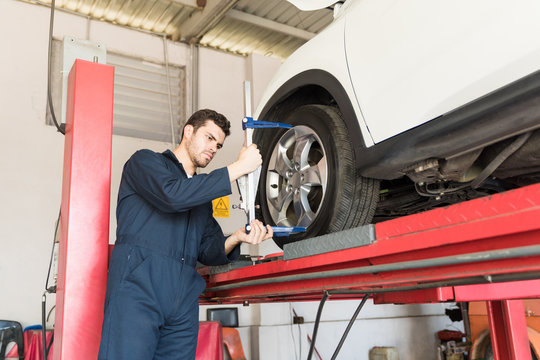 Automobile Worker Using Camber Caster Adapter On Tire