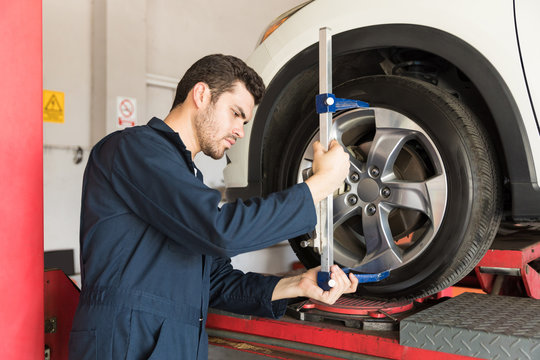 Engineer Checking Alignment Of Tire With Camber Caster Adapter
