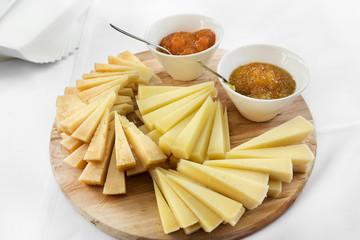 formaggi misti a spicchi con salse dolci sul tagliere