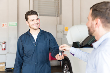 Smiling Technician Receiving Car Key From Customer At Repair Shop