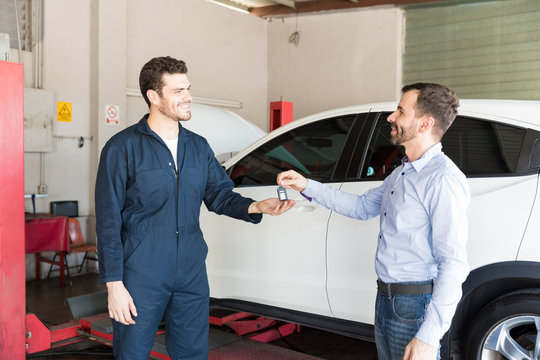 Customer Handing Key To Mechanic By White Car In Garage