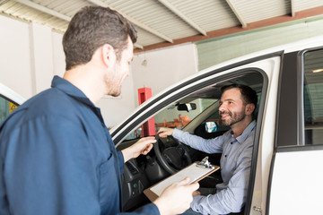 Service Man Talking With Client In Car At Repair Shop