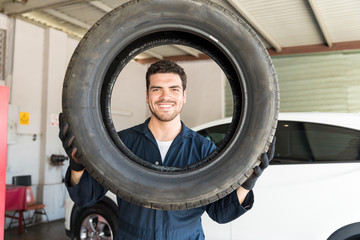 Smiling Mechanic Looking Through Car Tire In Auto Repair Shop