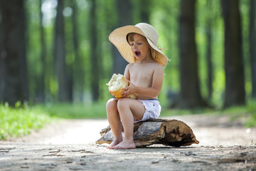 Young beautiful toddler girl sitting on a wooden log eating bread