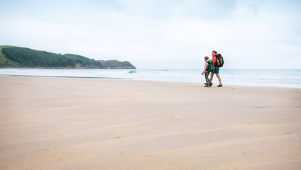 Mother and son walks together on sandy beach on the famous Camino del Norte Way, Spain