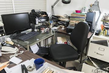 Messy business office desk with piles of files and disorganized clutter.