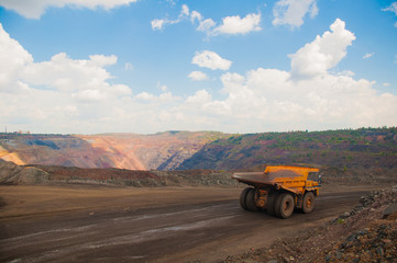 The work of a heavy quarry dump truck in the iron ore quarry.
