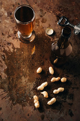 top view of peanuts, bottle opener and beer on rust surface