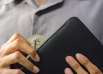 Businessman holding Physical Bitcoin from his wallet