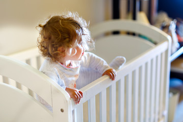 Cute little baby girl lying in cot after sleeping. Healthy happy child in bed climbing out.