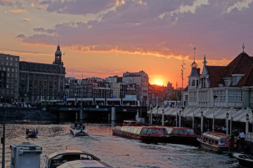 Spectacular view of Amsterdam river cruise boats and architecture at sunset.