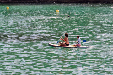 woman with a child surfing in the sea