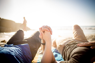 Close up image of a gay male couple holding hands on the beach in cape town south africa