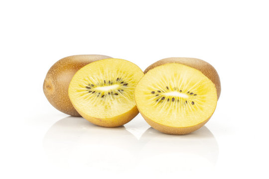 Group of two whole two halves of fresh golden brown kiwi fruit sungold variety one sliced isolated on white