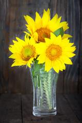 Bouquet of sunflowers in glass vase on dark wooden background, vertical image