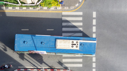 Top view aerial photo of a driving motorcycle and bus on asphalt track and pedestrian crosswalk in traffic road with light and shadow silhouette