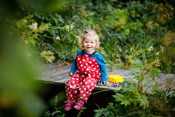 Cute adorable toddler girl sitting on wooden bridge and throwing small stones into a creek. Funny baby having fun with outdoor games in nature.