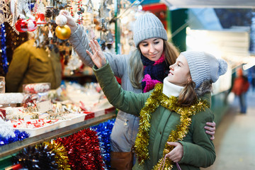 Smiling female and her daughter are choosing decorations for Christmas tree in the market outdoor.