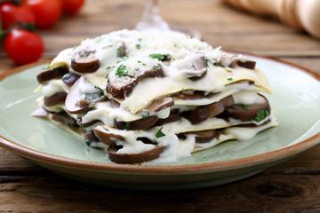 lasagne con funghi e besciamella su sfondo rustico