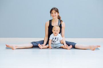 Happy smiling mother training fitness yoga stretching exercise with sweet positive emtions toddler blond baby boy at home over gray wall background. Fitness, maternity and healthy lifestyle concept.
