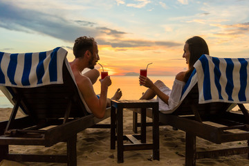 Rear view of a young romantic couple in love sitting on wooden chairs, while drinking cocktails on a tropical beach at sunset during vacation or honeymoon in Indonesia