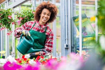 Beautiful young woman smiling during work as florist while watering various potted houseplants for sale in a modern flower shop