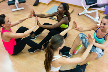 Cheerful woman clapping the hands of her workout partner after crunch exercise, during group class for core training in a modern fitness club for women only