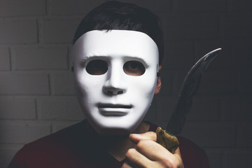 man in white mask threatens with knife