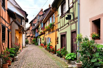 Fototapete - Colorful street in the of the town of Eguisheim, Alsace, France with timbered houses