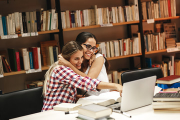 Two female students study in the school library.Learning and preparing for university exam.Hugging each other.Best friends concept.