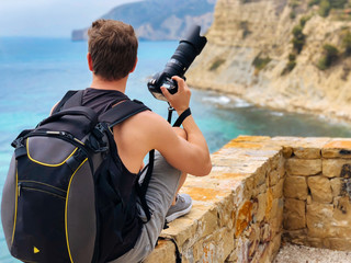 man with camera looking the view at sea coast