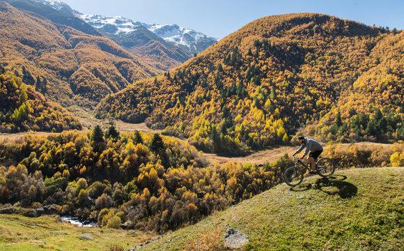 Mountain biker riding on bike in autumn  mountains