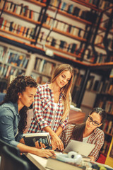 Cute female students study in the university campus library.Learning and preparing for exam.