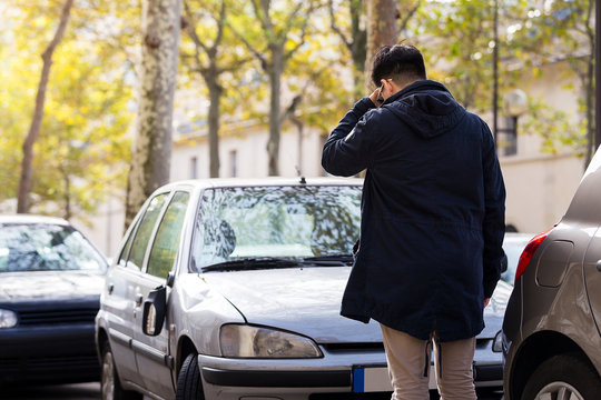 serious man stand in fron of his broken car in autumn at Paris,