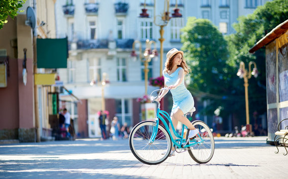 Young woman in a dress and a hat looking around while cycling in the city center copyspace lifestyle travelling youth femininity elegance transportation.