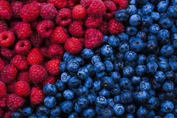 Blueberries and raspberries background. Top view.
