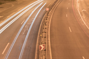 Road at night with long exposure and traces of automobile headlights.