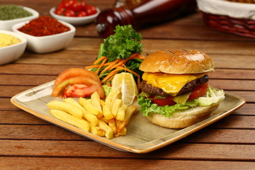 Tasty Cheeseburger and french fries on wood plate