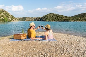 Pareja brindando mientras se cogen de la mano en la playa de un bonito lago.