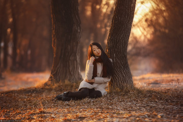 A beautiful Asian girl in Marsala scarf and gloves in an Autumn morning. A long black haired Korean girl in beige woolen coat standing in a fall park looking far away. Half length portrait. Nature.